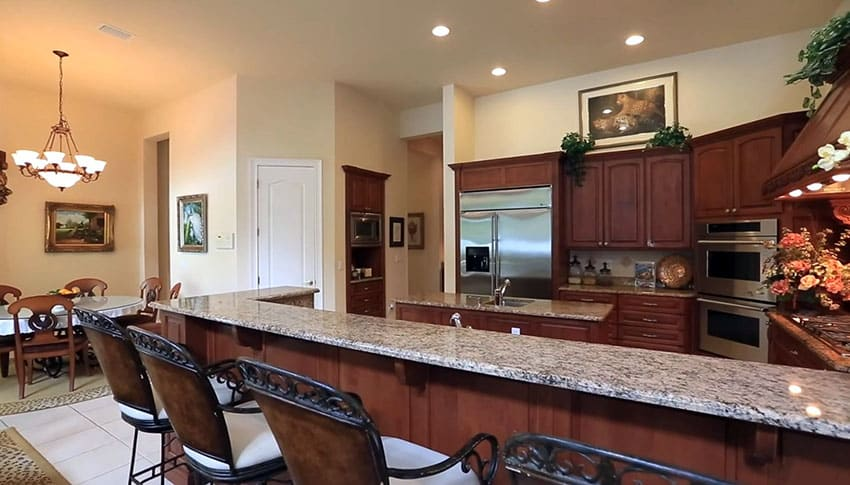 Kitchen with long dining peninsula and open concept to informal dining area