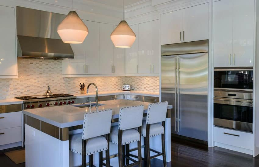 Kitchen with transitional design, high gloss white cabinets, penant lighting and quartz counter island
