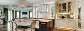 kitchen-with-white-flat-panel-cabinets-and-large-island-with-built-in-seating-bench