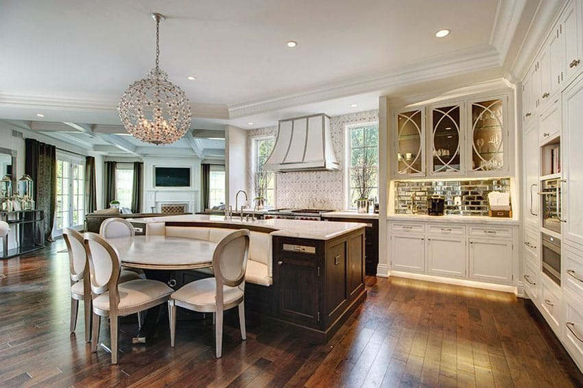 Kitchen with white flat panel cabinets and large island with built in seating bench