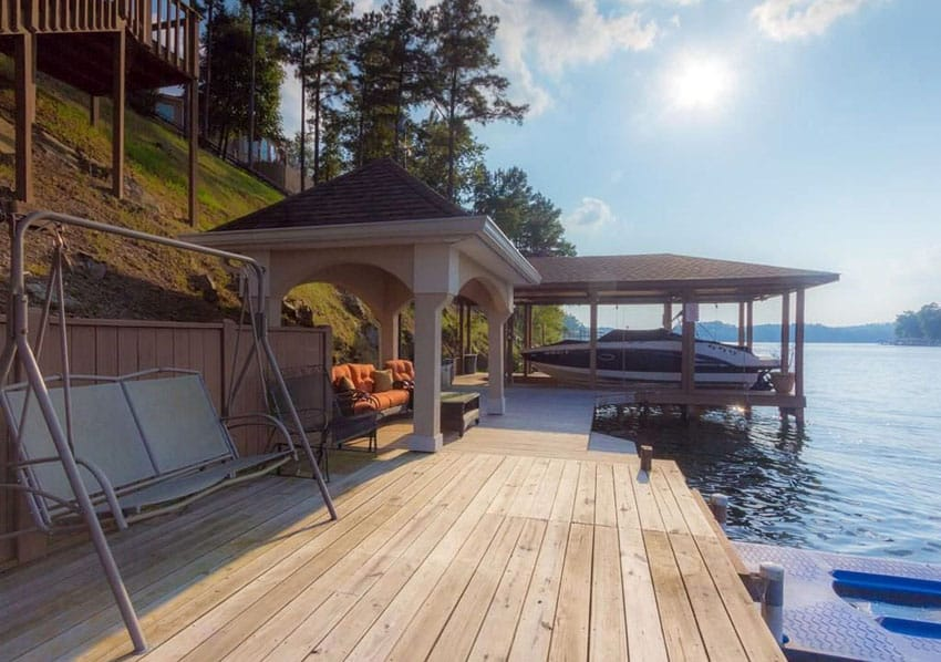Lake side deck with wood gazebo and sitting area next to boat house