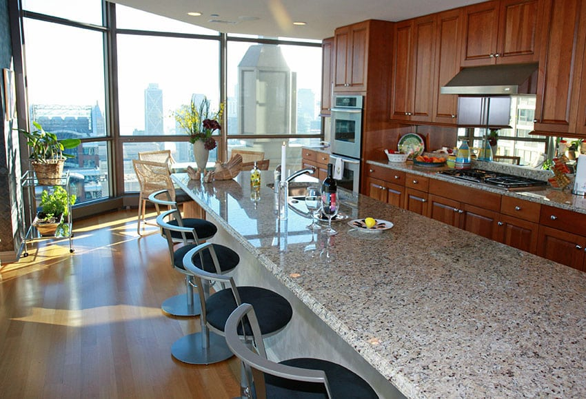 Large kitchen island with light granite counter and modern seating