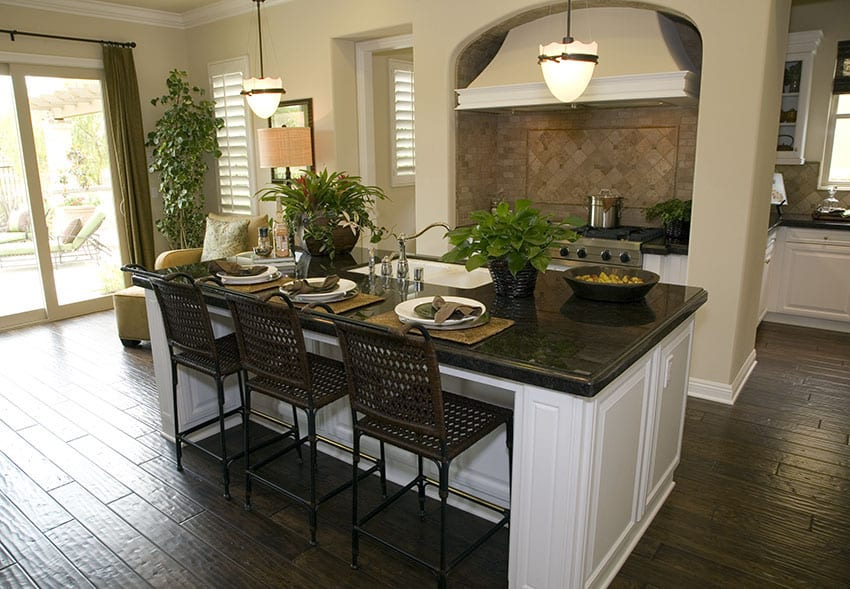 Large kitchen island with white cabinet dark counter and seating