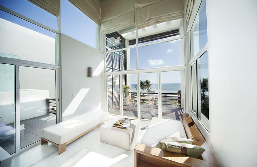 Living room with ocean view and high ceiling with door to outdoor patio