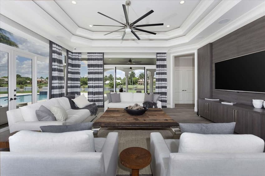 Living room with white furniture, hickory wood floors and high tray ceiling
