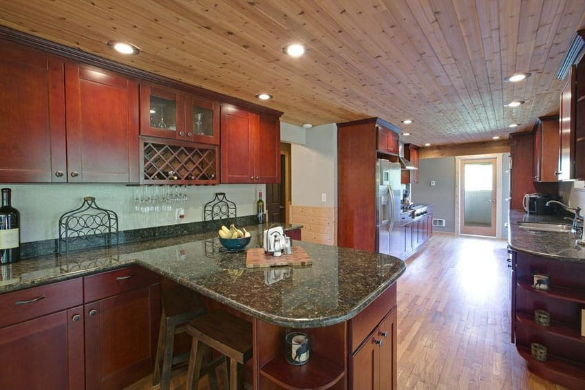 Long galley kitchen with small peninsula and ubatuba granite countertop
