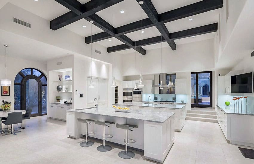Luxury contemporary kitchen with two islands, carrara marble counters and wood beam ceiling