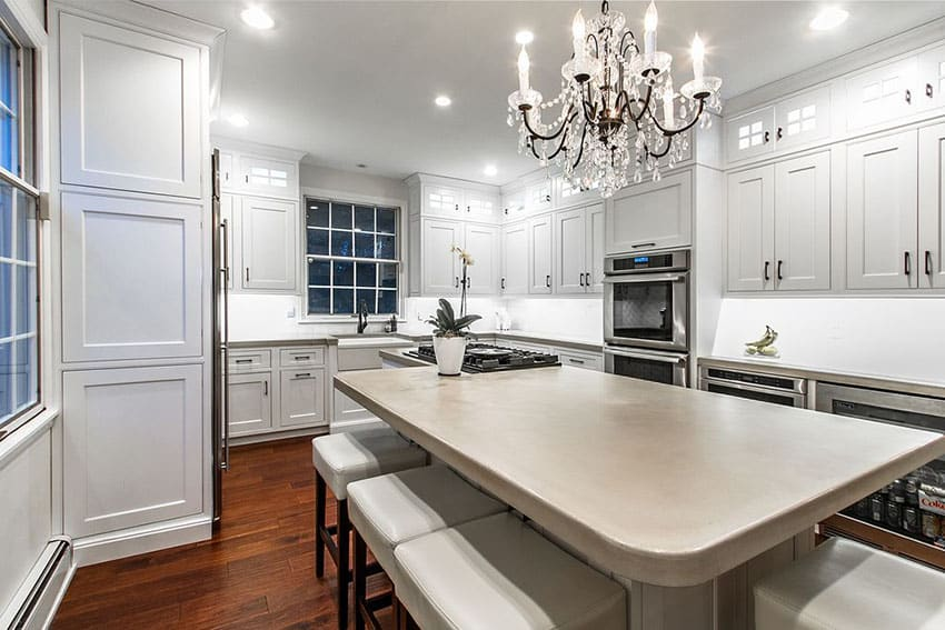 Luxury kitchen with concrete counter island with breakfast bar, chandelier and white cabinetry