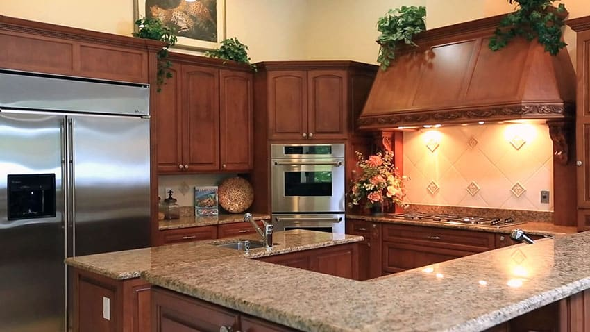 Luxury kitchen with custom exhaust hood and brown granite countertops