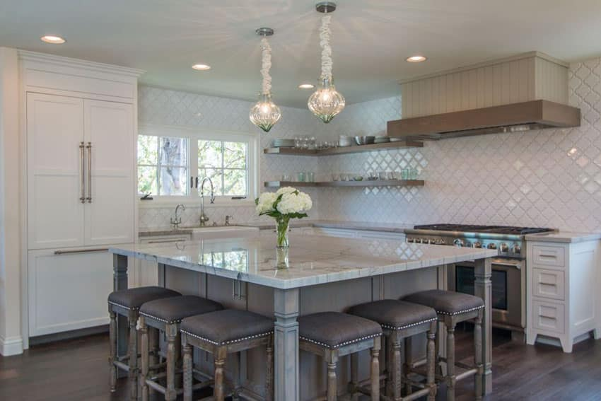 Luxury kitchen with large breakfast bar island topped with carrara white marble counter and pendant lights