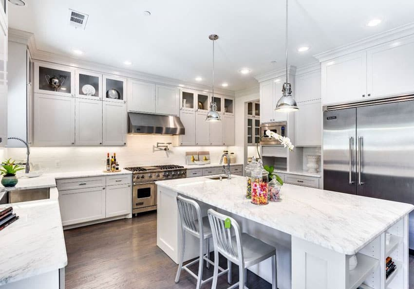 Luxury kitchen with white cabinetry, large marble topped island with vintage pendant lighting and wood floors