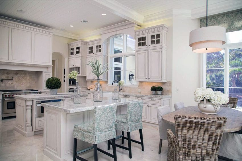 Luxury traditional kitchen with two islands, damasco white marble counters and white cabinetry with glass doors