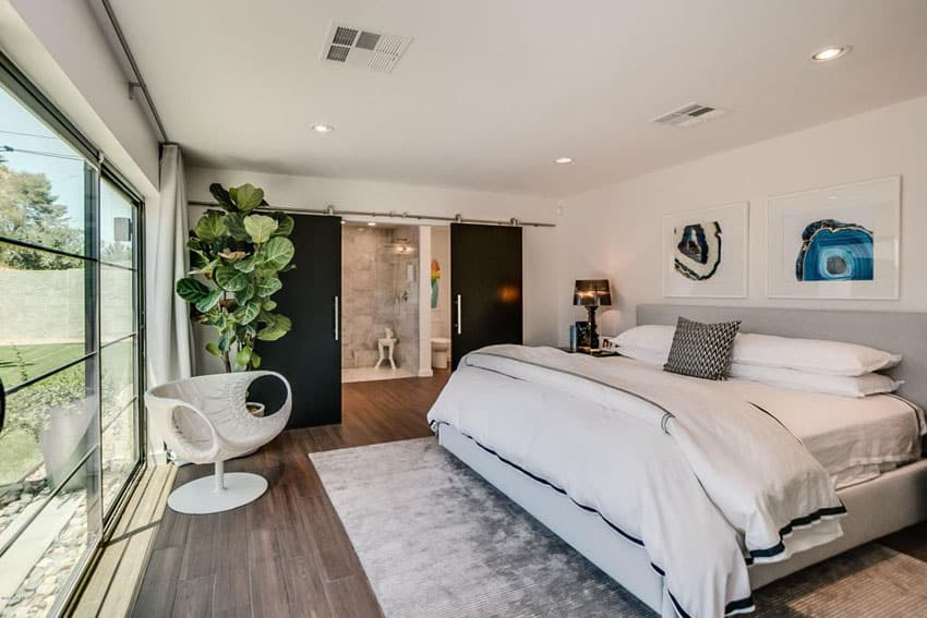 Master bedroom with black sliding barn doors leading to bathroom