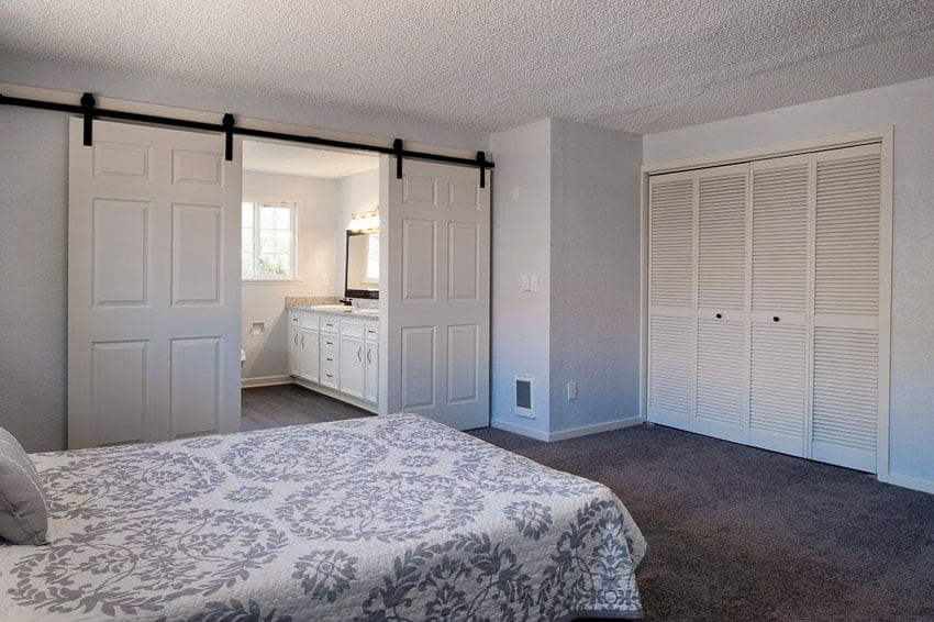 Master bedroom with hollow core sliding barn doors in white with black rail