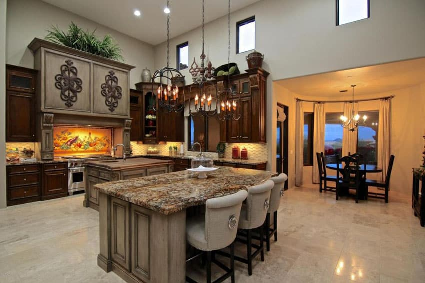 Mediterranean kitchen with butcher block island and breakfast bar island with granite counter