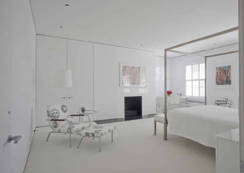 Modern bedroom with high glass white built-in storage walls and metal canopy bed