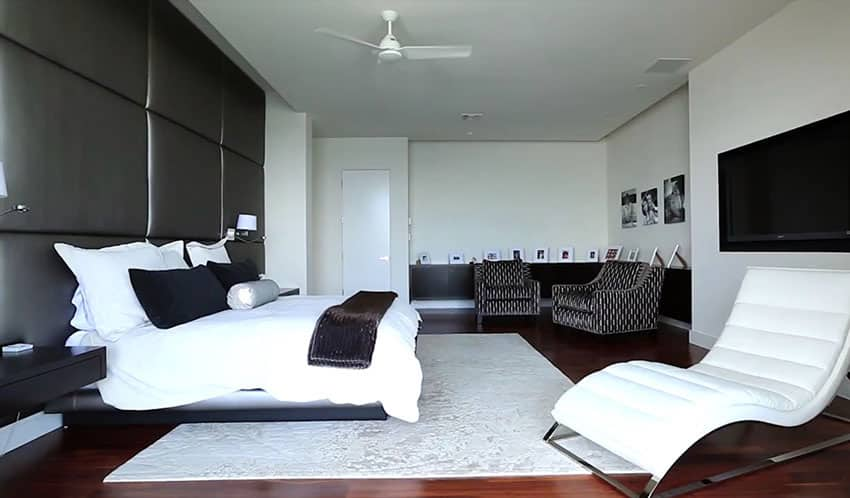 Modern bedroom with padded black accent wall and black decor