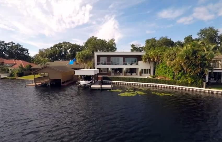 Modern home with lake front backyard and boathouse