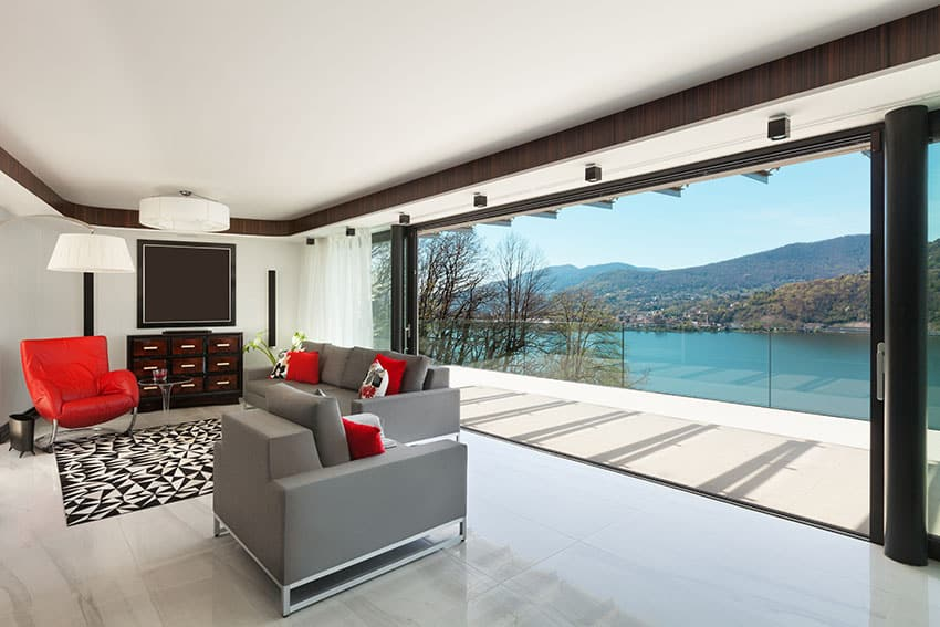 Modern lake view living room with red and gray furniture