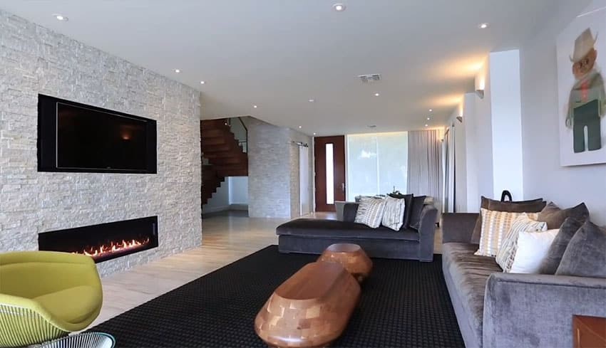 Modern living room with stacked stone fireplace wall with casual furniture