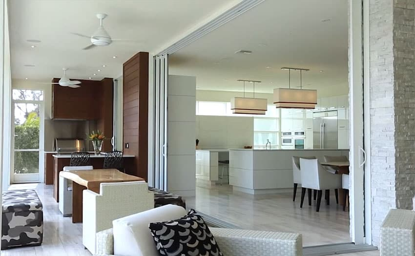 Modern outdoor kitchen with covered patio flows into modern white kitchen through large sliding doors