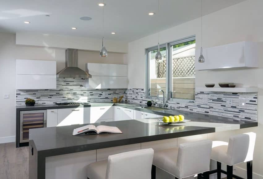 Modern u shaped kitchen with gray quartz counter, mosaic tile backsplash, pendant lights and armless stools