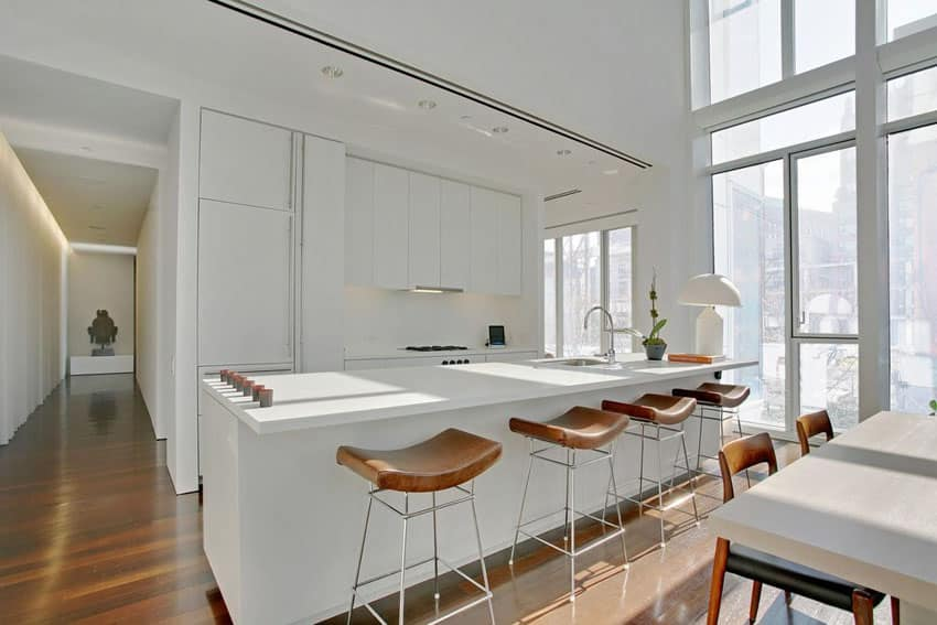 Modern white kitchen with quartz counters, flat panel cabinets and open dining area