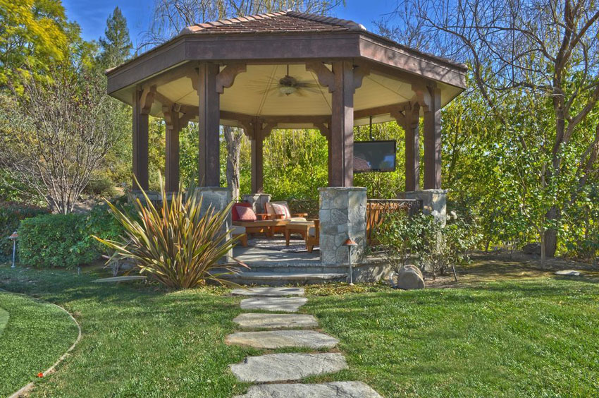 Pathway leading to large gazebo with outdoor lounge furniture