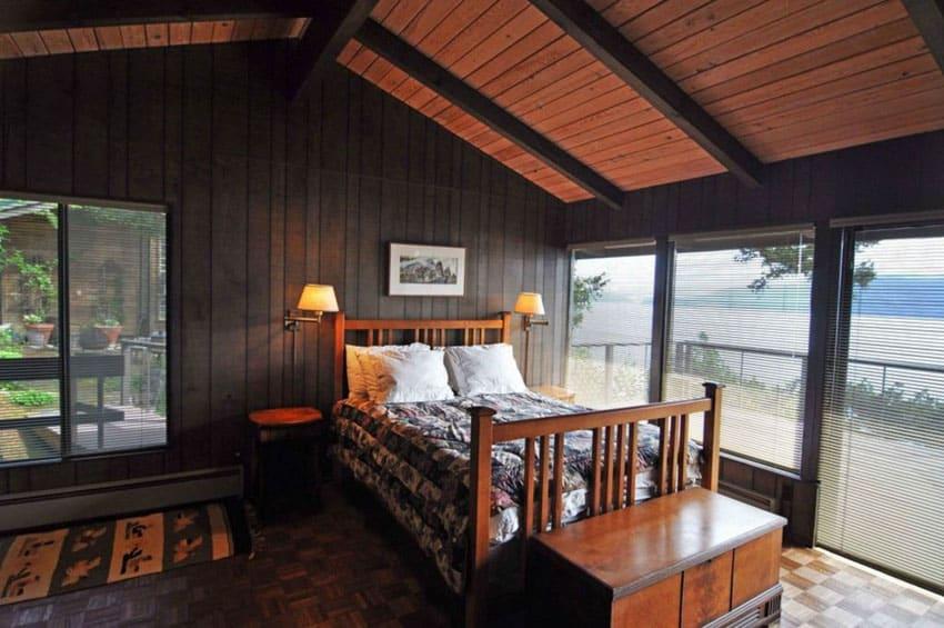 Rustic black painted bedroom with lake views