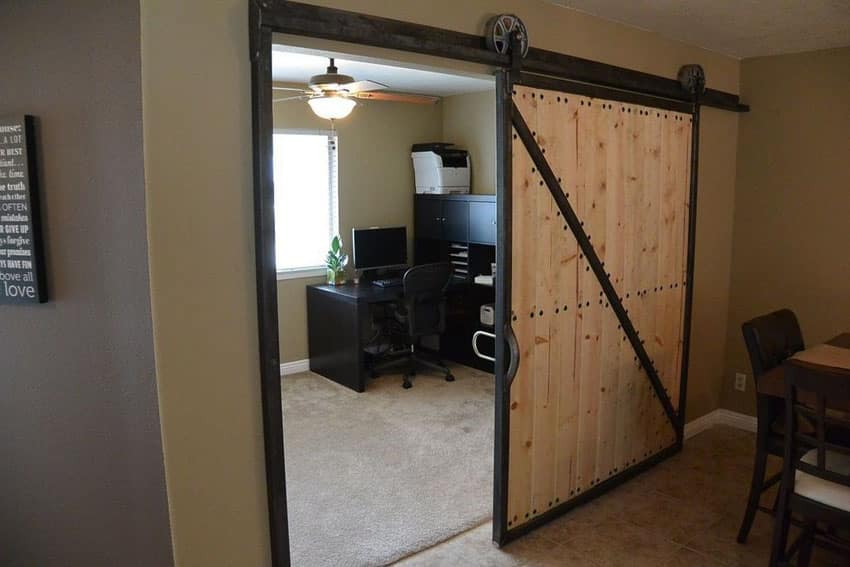Rustic top mount sliding barn door leading to home office
