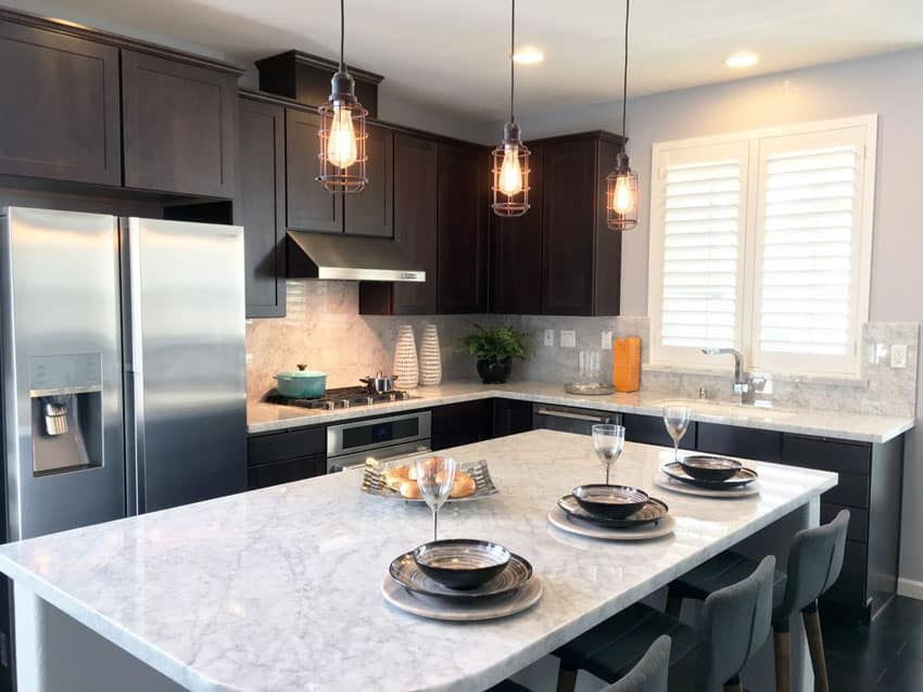 Small contemporary kitchen with calacatta carrara marble counter dark cabinets and edison lights