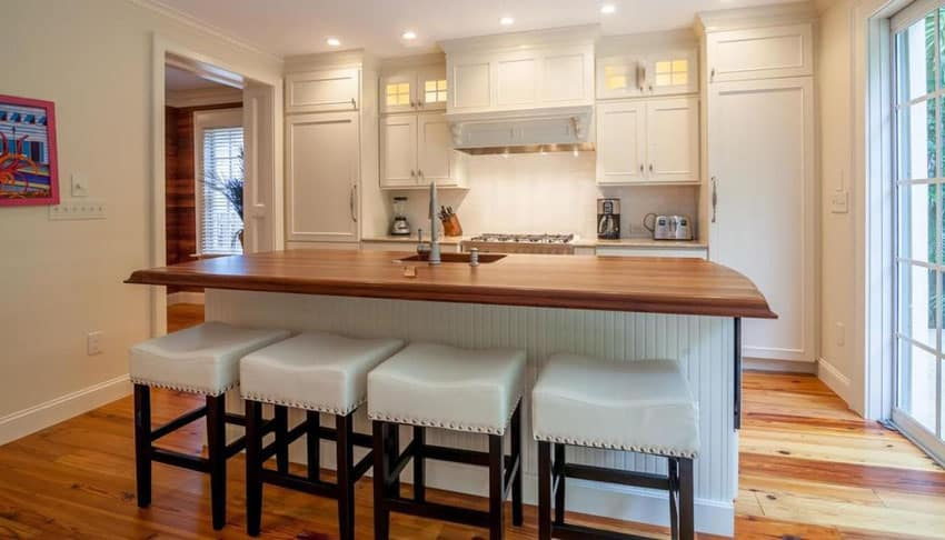 Small cottage style kitchen with large butcher block island