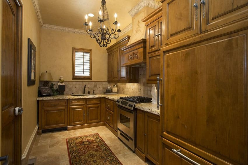 Small Mediterranean kitchen with new venetian gold granite counter and travertine floors