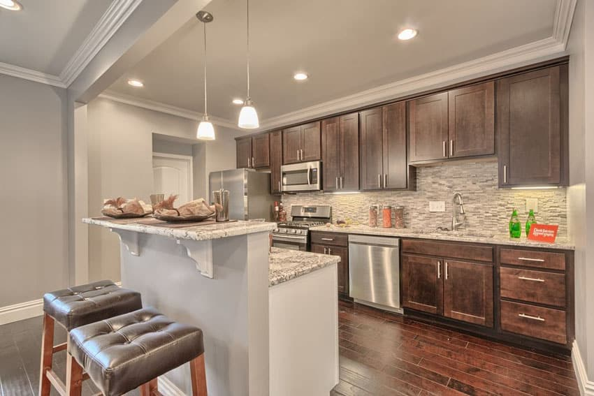 Small transitional kitchen with moon white granite counter and breakfast bar