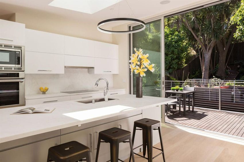 Small white modern kitchen with island and view to patio