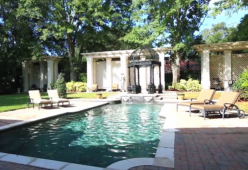 Swimming pool with custom wrought iron gazebo in front of long pergola sun shade