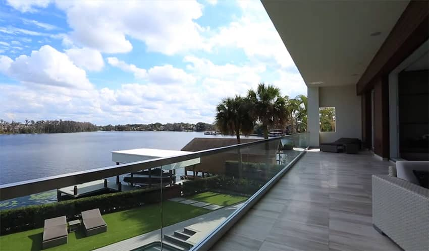 Top floor patio view of lake from modern home with glass railings and outdoor chairs