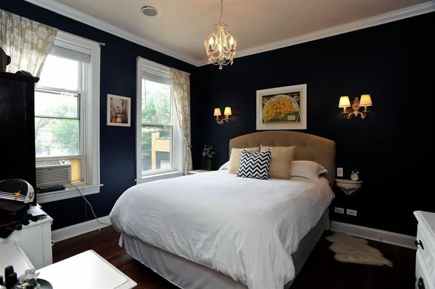 Traditional bedroom with dark walls, white molding and mini chandelier