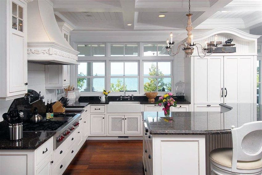 Traditional kitchen with angola black granite counters, curved breakfast bar island, chandelier and ocean views