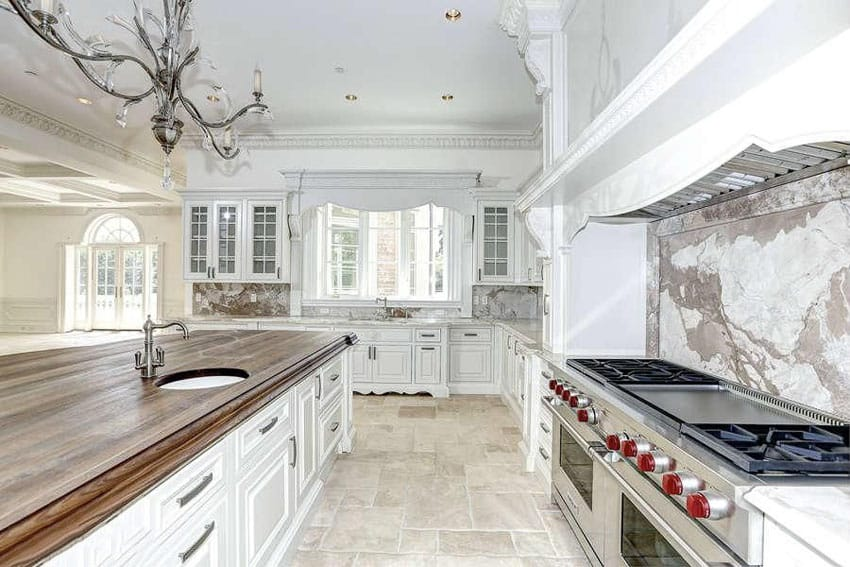 Traditional kitchen with butcher block wood island, decorative molding and marble backsplash