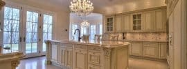 traditional-kitchen-with-cream-cabinets-chandelier-crema-marfil-marble-counter-and-large-island