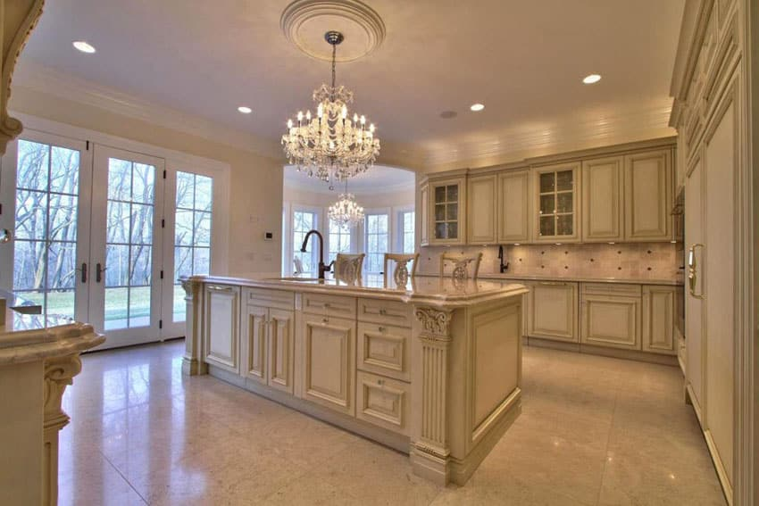 Traditional kitchen with cream cabinets, chandelier, crema marfil marble counter and large island