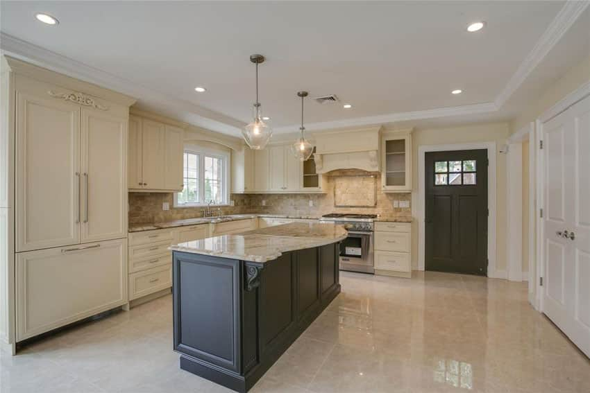 Traditional kitchen with cream recessed panel cabinets and dark wood island with calacatta gold marble