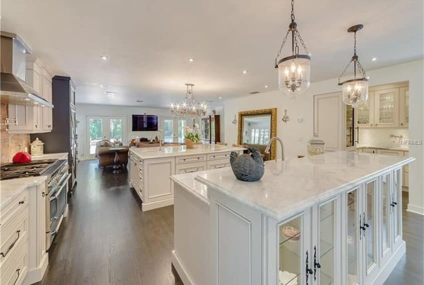 Traditional kitchen with dual islands with calacatta carrara marble countertops, chandelier and white oak flooring