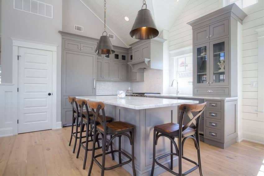 Traditional kitchen with gray cabinets white marble counter and metal funnel pendant lights