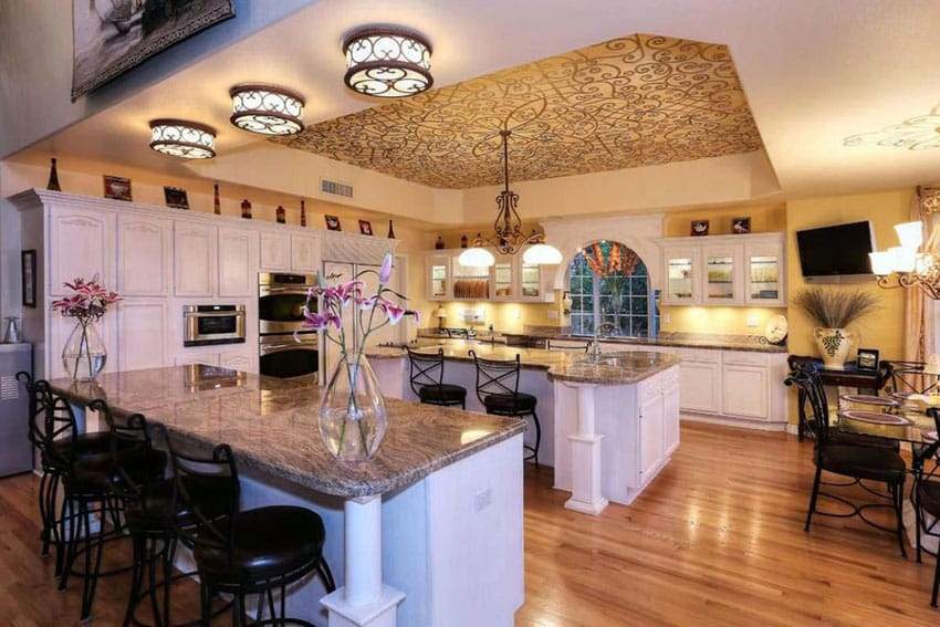 Traditional kitchen with white cabinets, granite counter breakfast bar with bar stools and center dining island