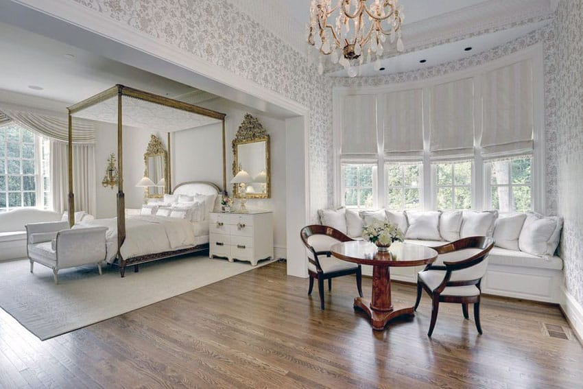 Traditional master bedroom with Georgian four poster bed chandelier and window seat sofa