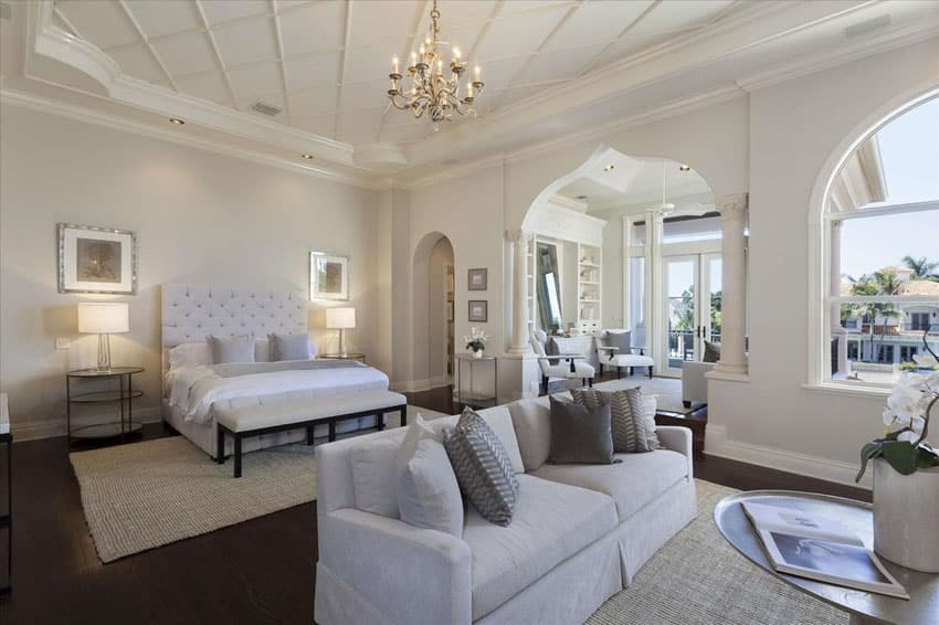 Traditional master bedroom with white fabric bed, sofa seat and chandelier