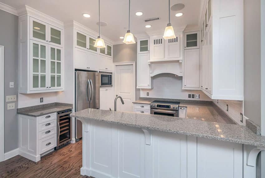 Traditional white cabinet kitchen with peninsula, granite counters and pendant lighting
