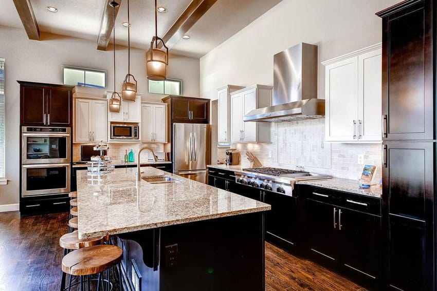 Transitional kitchen design with african rainbow granite counters, dark shaker cabinets and mini pendant lights